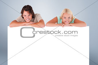 Composite image of smiling couple leaning on a whiteboard