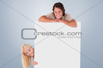 Composite image of smiling couple with whiteboard