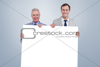Composite image of smiling tradesmen holding blank sign