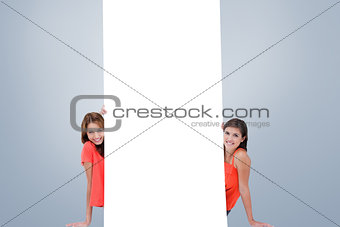 Composite image of two smiling teenage girls sitting behind a blank poster