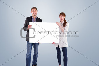 Composite image of smiling couple holding large sign