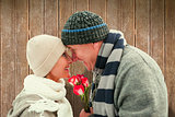 Composite image of happy mature couple in winter clothes with roses