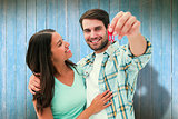 Composite image of happy young couple showing new house key