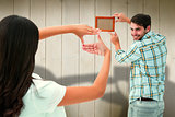 Composite image of happy young couple putting up picture frame