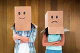 Composite image of young couple wearing sad face boxes over head