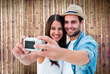 Composite image of happy hipster couple taking a selfie