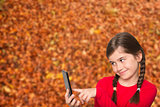 Composite image of cute little girl using smartphone