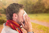 Composite image of man blowing nose on tissue