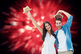 Composite image of happy hipster couple smiling at camera and cheering