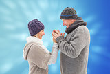 Composite image of happy mature couple in winter clothes embracing