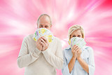 Composite image of happy mature couple smiling at camera showing money