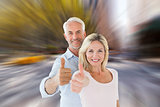 Composite image of smiling couple showing thumbs up together