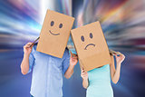 Composite image of couple wearing sad face boxes on their heads