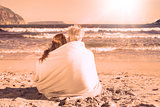 Couple sitting on the beach under blanket looking out to sea