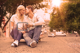 Cute young couple sitting on skateboard kissing