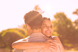 Loving and happy woman embracing man at park