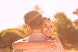 Loving and happy woman embracing man at park