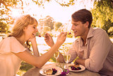 Cute couple feeding each other dessert