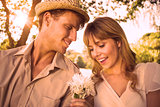 Smiling man offering his girlfriend a white flower in the park