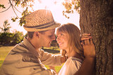 Cute smiling couple leaning against tree in the park