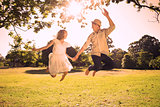 Cute couple jumping in the park together holding hands