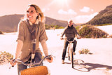 Carefree couple going on a bike ride on the beach