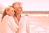 Happy couple hugging on the beach looking out to sea