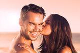 Attractive woman kissing her boyfriend on the cheek