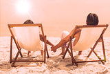Couple lying on deck chairs