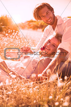 Attractive couple relaxing in the countryside smiling at camera