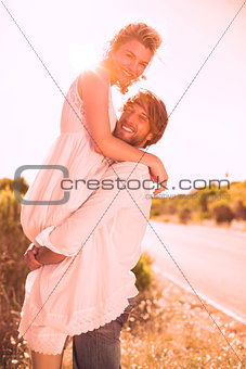 Attractive man lifting up his girlfriend smiling at camera