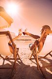 Couple clinking their glasses while relaxing on their deck chairs