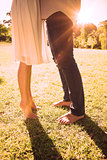Couples bare feet standing on grass