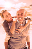 Happy hugging couple on the beach looking at camera