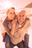Laughing couple smiling at camera on the beach