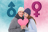 Composite image of happy couple in warm clothing holding heart
