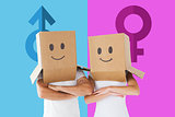 Composite image of couple wearing smiley face boxes on their heads
