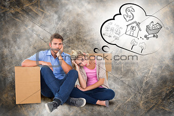 Composite image of unhappy young couple sitting beside moving boxes