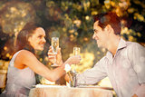 Couple with champagne flutes sitting at outdoor café