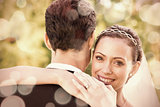 Portrait of happy bride embracing groom