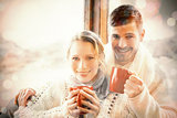 Loving couple in winter clothing with coffee cups against window