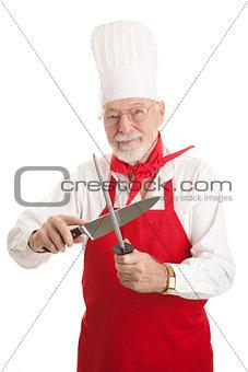 Mature Chef Sharpens Knife