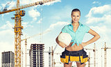 Woman in tool belt holding helmet under his arm. Looking at camera, smiling. Construction site as backdrop