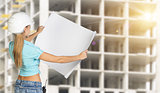 Woman in helmet standing backwards and holding paper sheet. Building under construction as backdrop