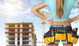 Woman in tool belt standing backwards, akimbo. Cropped image. Building under construction as backdrop