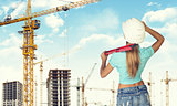 Woman in helmet stands backwards, holding building level. Looks at crane. Construction site as backdrop
