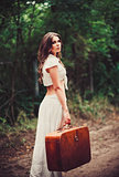 Beautiful young sad woman with suitcase in hand standing on road