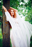 Lovely ginger woman wearing white dress stands near tree