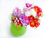 Beautiful bouquet of colorful freesia in green vase on a white b