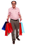 Happy matured man carrying shopping bags